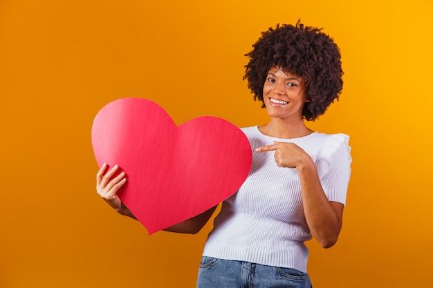 Fotoportret van glimlachende afrovrouw die grote rode hartkaart houdt