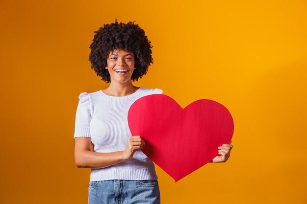 Fotoportret van glimlachende afrovrouw die grote rode hartkaart houdt Premium Foto