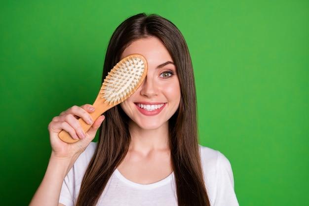 Fotoportret van lachend meisje dat één oog bedekt met haarborstel geïsoleerd op een levendige groen gekleurde achtergrond