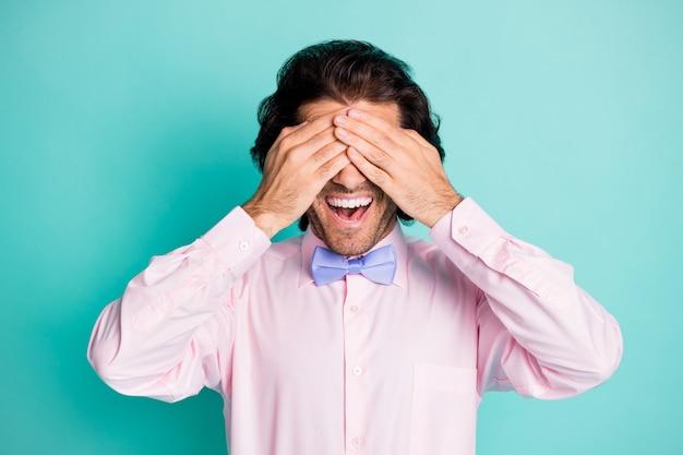 Fotoportret van man die ogen bedekt met twee handen geïsoleerd op pastel cyaan gekleurde achtergrond