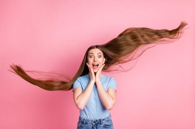 Fotoportret van meisje met vliegend haar dat gezicht aanraakt met twee handen geïsoleerd op pastelroze gekleurde achtergrond