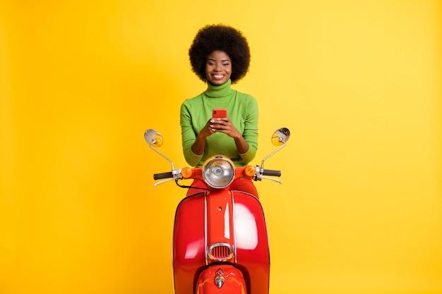 Fotoportret van opgetogen jong donkerbruin meisje met zwarte huid in casual outfit op rode scooterboekingsreis via smartphone geïsoleerd op levendig geel gekleurde achtergrond