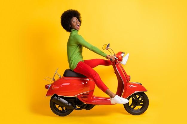 Fotoportret van opgewonden afro-amerikaanse vrouw die een rode scooter bestuurt met gespreide benen in een casual outfit geïsoleerd op een levendige geel gekleurde achtergrond