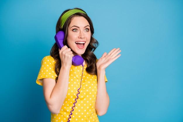 Fotoportret van opgewonden meisje dat goed nieuws hoort over paarse telefoon geïsoleerd op pastel lichtblauw gekleurde achtergrond