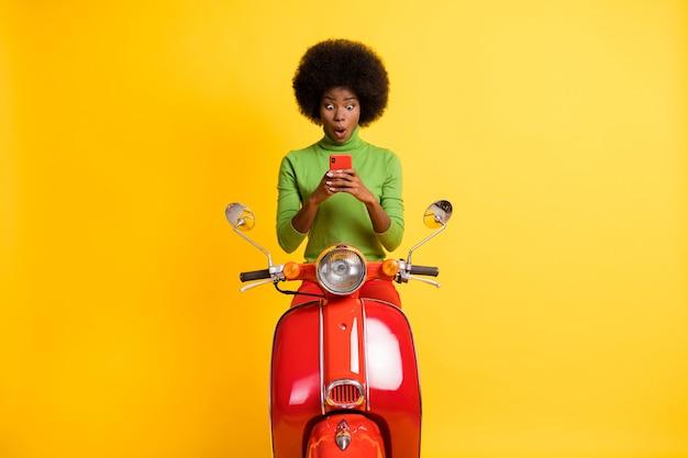 Fotoportret van opgewonden motorrijder op motorfiets met mobiele telefoon in twee handen met een casual groene trui geïsoleerd op een levendige geel gekleurde achtergrond