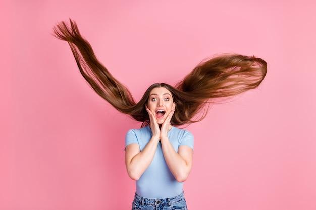 Fotoportret van schreeuwend meisje dat gezicht aanraakt met twee handen met vliegend haar geïsoleerd op pastelroze gekleurde achtergrond