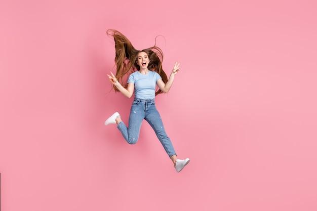Fotoportret van schreeuwend meisje dat twee v-tekens toont die omhoog springen geïsoleerd op pastelroze gekleurde achtergrond