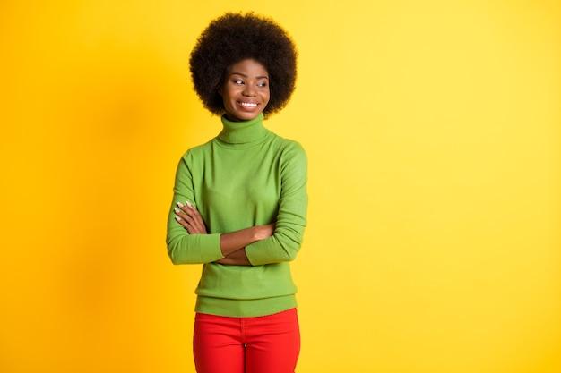 Fotoportret van serieuze afro-amerikaanse vrouw met gekruiste armen die naar de zijkant kijkt geïsoleerd op een levendige geel gekleurde achtergrond
