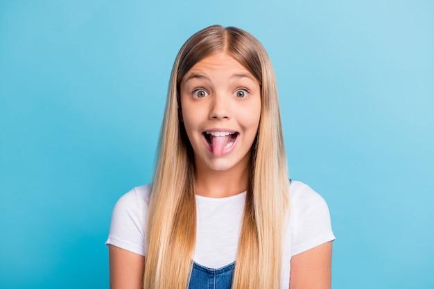 Fotoportret van speelse jongen die tong toont geïsoleerd op pastelblauw gekleurde achtergrond