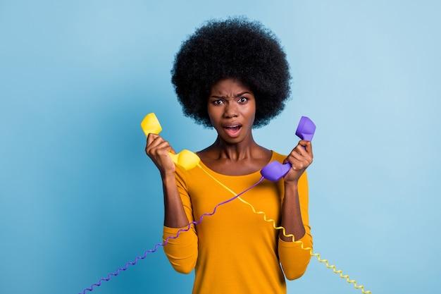 Fotoportret van teleurgestelde geïrriteerde, gestresste vrouw met zwarte huid die retro-telefoontoestellen vasthoudt die op een levendige blauwe kleurachtergrond worden geïsoleerd