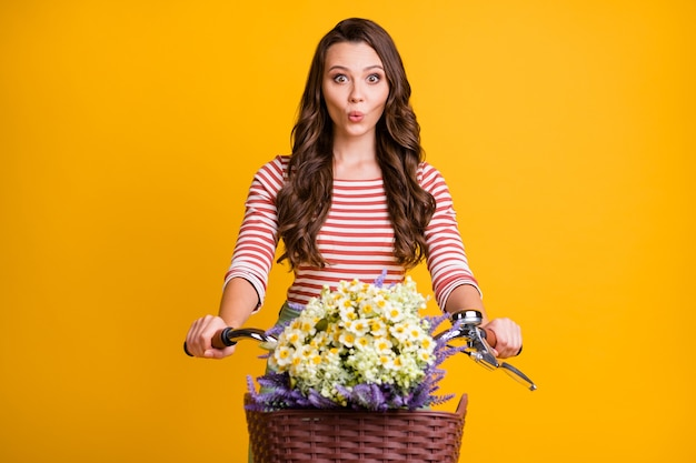 Fotoportret van verrast meisje dat handen op de fiets houdt met een mand met wilde bloemen geïsoleerd op een felgele achtergrond