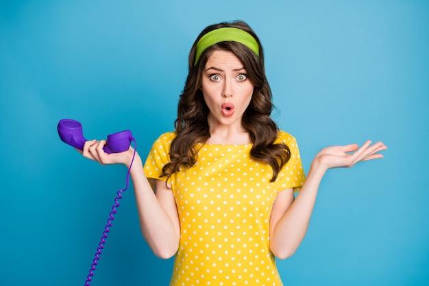 Fotoportret van verward meisje met telefoon in één hand geïsoleerd op pastel lichtblauw gekleurde achtergrond