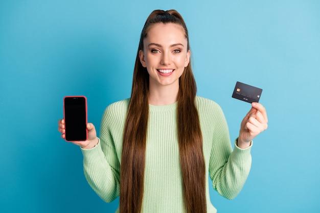 Fotoportret van vrouw met telefoon met lege ruimtekaart geïsoleerd op pastelblauw gekleurde achtergrond