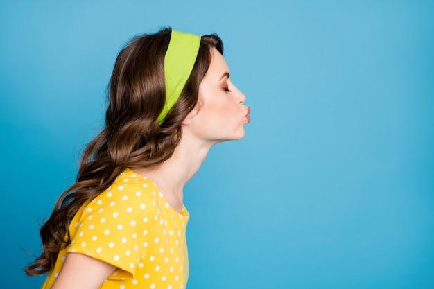 Fotoportretprofiel van schattig meisje dat luchtkus verzendt geïsoleerd op pastel lichtblauw gekleurde achtergrond