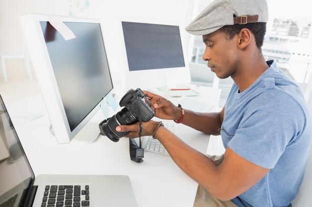 Fotoredacteur die digitale camera in bureau bekijken