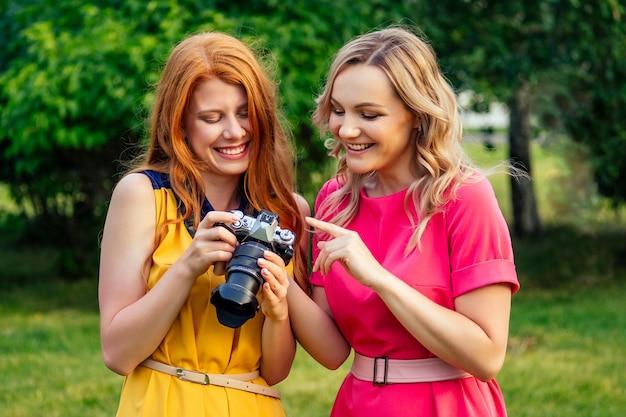 Fotosessie mooie jonge gember roodharige ierse meisje in een gele jurk en europese blonde vrouw in roze jurk fotografeerden elkaar in het zomerpark. fotoshoot van twee modelvriendinnen