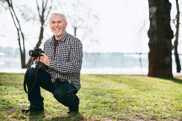 Fotosessie. vrolijke senior man grijnzend en met behulp van camera