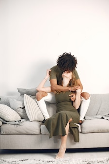 Fotoshoot. gelukkige jonge paar thuis op de bank. knuffelen, zoenen.