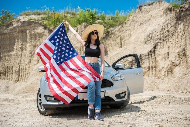 Fotoshoot van een charmante dame met de amerikaanse vlag bij de auto in een zandgroeve in de zomer