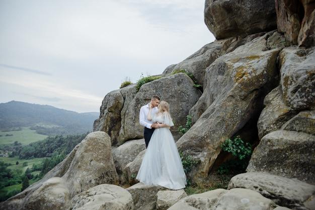 Fotoshoot van een verliefd stel in de bergen. het meisje is gekleed als een bruid in een trouwjurk.
