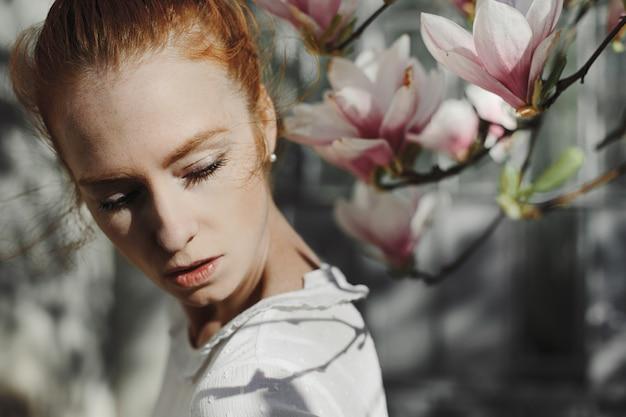 Fotoshoot van roodharige vrouw in de buurt van een magnolia bloemen