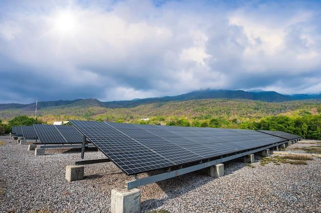 Fotovoltaïsche modules zonne-energiecentrale in groene boom bij landschap uitzicht op het meer natuur bos uitzicht op de bergen lente met witte wolk achtergrond, alternatieve energieconcept en schone energie.