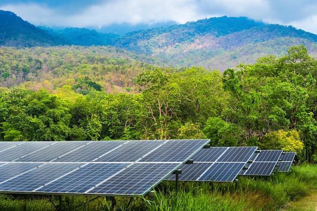 Fotovoltaïsche modules zonne-energiecentrale in groene boom op landschap uitzicht op het meer natuur bos uitzicht op de bergen lente met witte wolk achtergrond