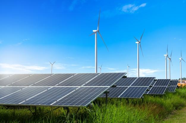 Fotovoltaïsche modules zonne-energiecentrale met windturbines op blauwe hemel
