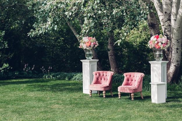 Fotozone met mooie fauteuil op een bruiloft versierd met bloemen en houten blokjes
