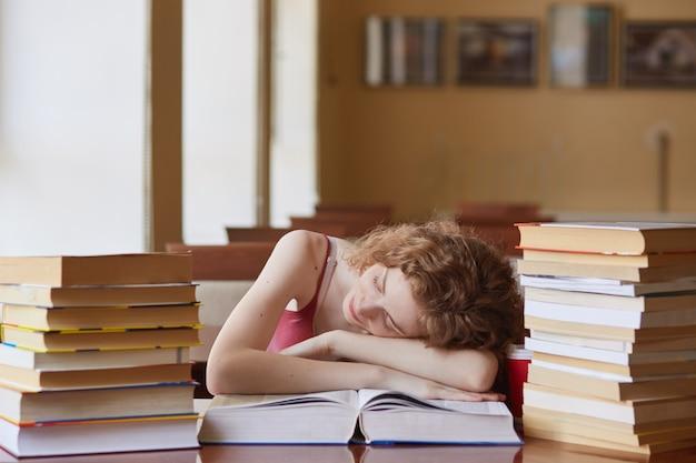 Foxy-haired vrouwelijke student in slaap vallen tijdens het lezen van boek voor het vinden van informatie