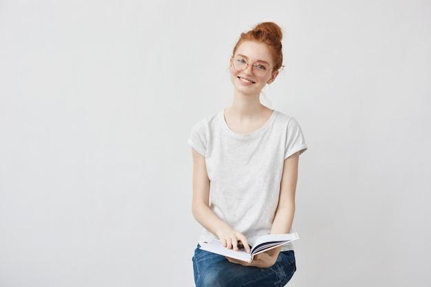 Foxy vrouwelijke student glimlachend bedrijf notebook.