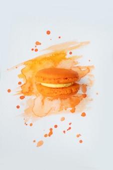 Fpink rench cookie macaroon op oranje aquarel achtergrond, bovenaanzicht