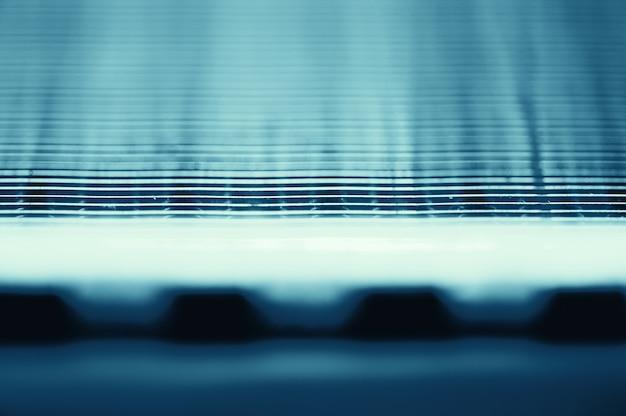 Fragment van automotive radiator in macro met kopie ruimte. zwart-wit beeld van metalen auto-onderdeel is close-up. lege oppervlakte van staaltextuur in blauwe toon.