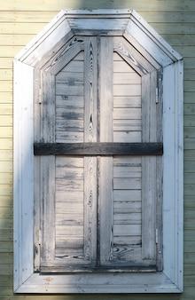 Fragment van de gevel van een oud houten huis met gesloten luiken en een gesloten raam. interieurdetails of achtergrond van oude huizen