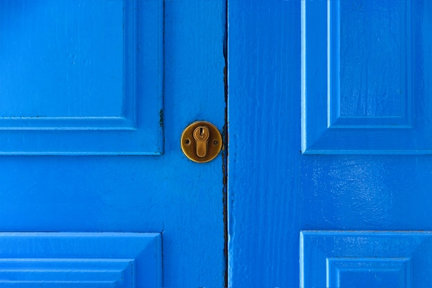 Fragment van een blauwe deur met een koperen slot