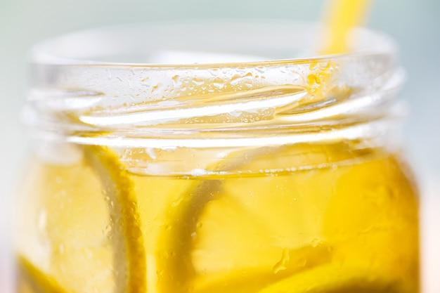 Fragment van een blikje koude limonade met een rietje