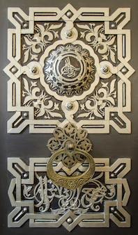 Fragment van een deur in oosterse stijl met ornament en arabisch schrift