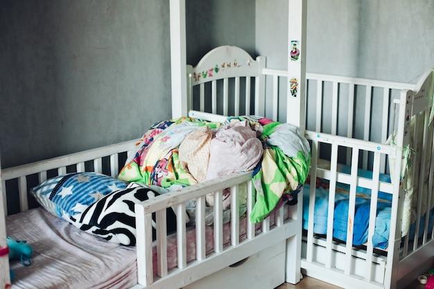 Fragment van een foto van een kinderkamer met verspreide dingen, kussens en dekbedden op de bedden