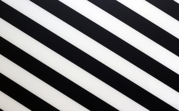 Fragment van een gestreept zwart-wit stuk van een plastiek als achtergrondtextuur