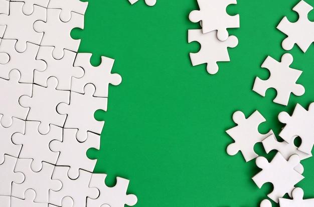 Fragment van een gevouwen witte legpuzzel en een stapel ongekamde puzzelelementen tegen de achtergrond