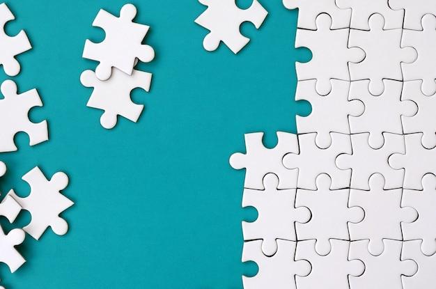 Fragment van een gevouwen witte legpuzzel en een stapel puzzelelementen met een niet-gecamoufleerde tekening