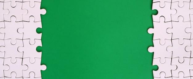 Fragment van een gevouwen witte puzzel op de achtergrond van een groene kunststof oppervlak