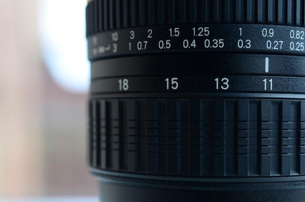 Fragment van een groothoekzoomlens voor een moderne spiegelreflexcamera. de reeks afstandswaarden wordt aangegeven door witte cijfers op de zwarte balk