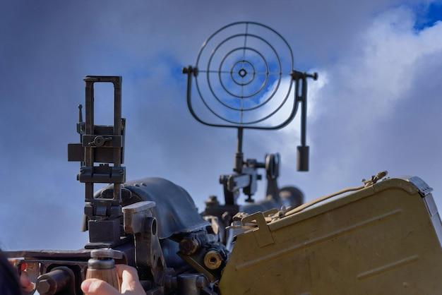 Fragment van een luchtafweermachinegeweer, een rond zicht is gericht op wolkenlucht