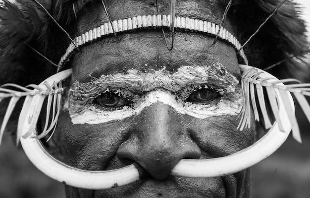 Fragment van een mannengezicht met traditionele kleuren en versieringen.
