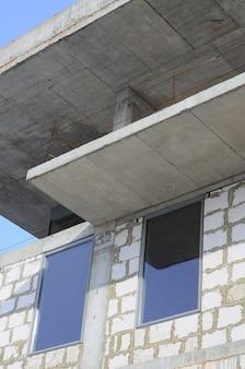 Fragment van een onafgewerkte structuur van een gebouw met meerdere verdiepingen gemaakt van grote betonnen bakstenen