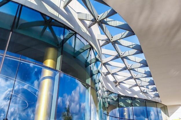 Fragment van gebogen glazen gevel van modern gebouw in zonlicht op een blauwe hemelachtergrond
