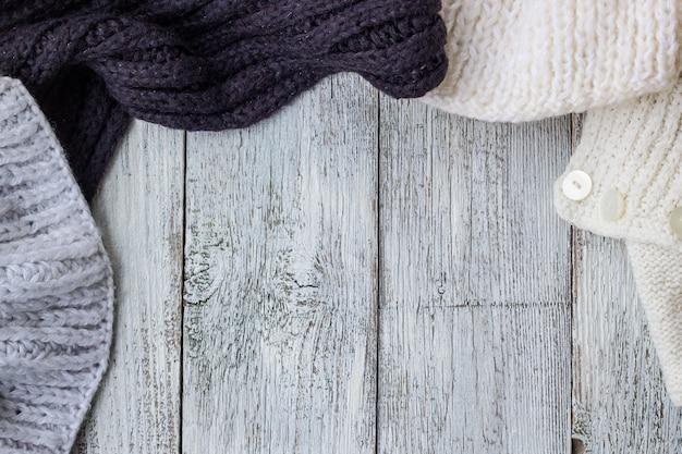 Fragment van het breien van kleren op witte houten achtergrond