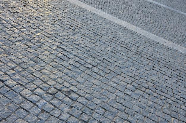 Fragment van het straatvierkant, gevouwen uit een grijze vierkante straatsteen