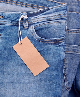 Fragment van jeans met een bruine papieren lege tag